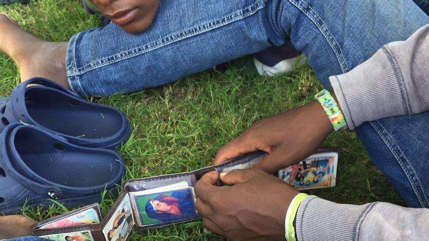 Un menor eritreo muestra las fotos de algunos de sus amigos y familiares refugiados en diferentes países del mundo: Sudán, Etiopía, Suecia, Alemania... | FOTO: Gabriela Sánchez