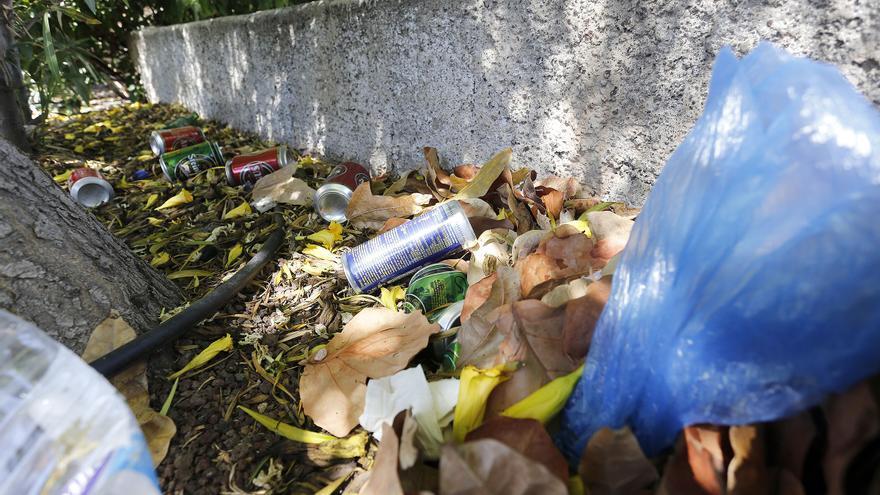 Basura acumulada junto a una pared de un jardín