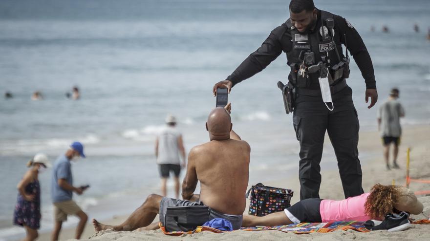 Un oficial de policía recuerda que no está permitido tomar el sol en Palm Beach, Florida, este 18 de mayo