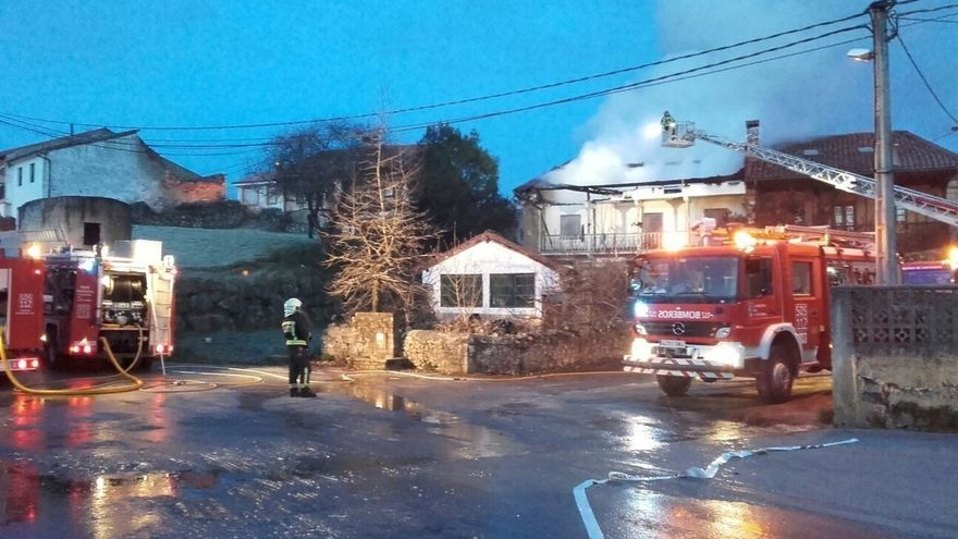 Bomberos trabajan en la extinción de un incendio en una vivienda de Udías que ha quedado inhabitable