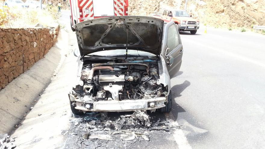 En la imagen, el coche calcinado junto a un vehículo de Bomberos La Palma.