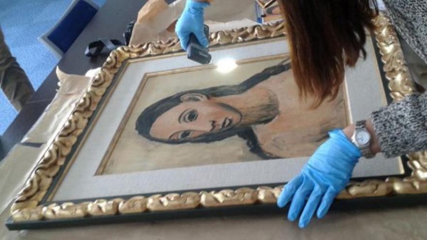 Expertos examinan el Picasso 'Cabeza de mujer joven' tras ser incautada en Calvi (Córcega). EFE