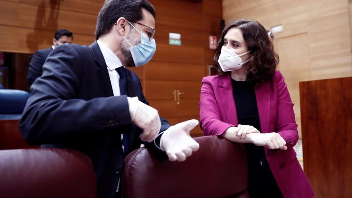 La presidenta de la Comunidad de Madrid, Isabel Díaz Ayuso (d) conversa con el consejero de Hacienda, Javier Fernández-Lasquetty (i) en la Asamblea de Madrid