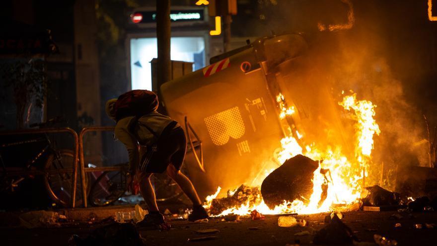 Un manifestante frente a un contenedor que arde durante los disturbios en la Plaza de Urquinaona, en Barcelona a 18 de octubre de 2019 / Europa Press