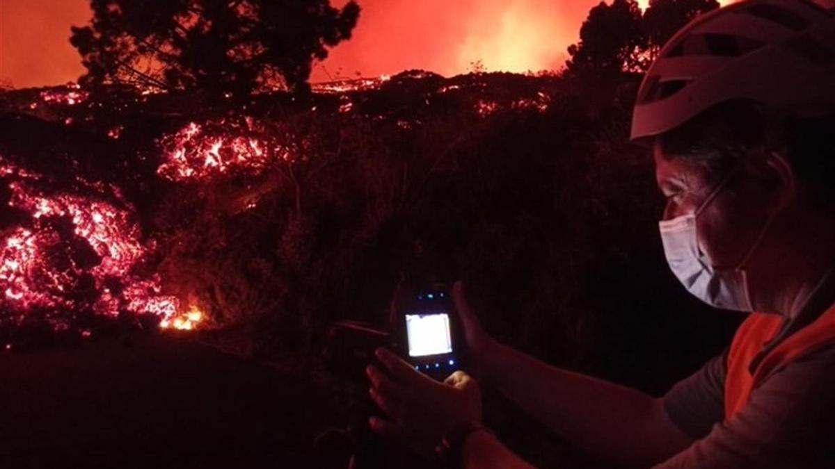 Un científico del Instituto Vocanológico de Canarias toma una imagen térmica de la colada del volcán de La Palma.