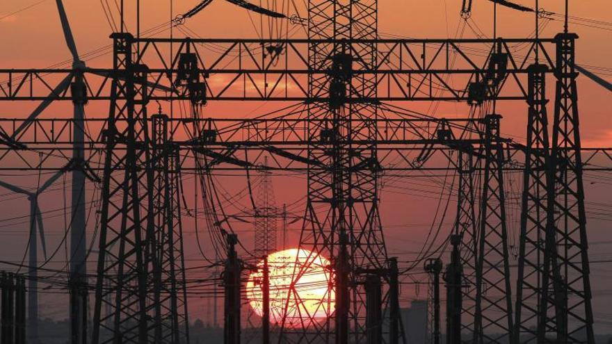 Una puesta de sol junto al tendido eléctrico y unos molinos de viento (izquierda). / Efe