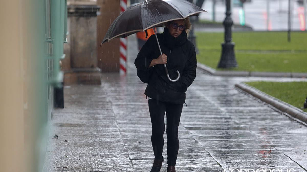 Una mujer se protege de la lluvia