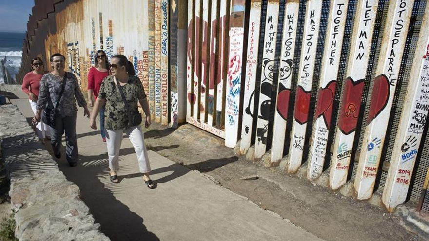 Unas personas pasan, este lunes 7 de noviembre 2016, delante de un mural pintado en el muro fronterizo a lo largo de la frontera entre Tijuana (México) y San Diego (California).