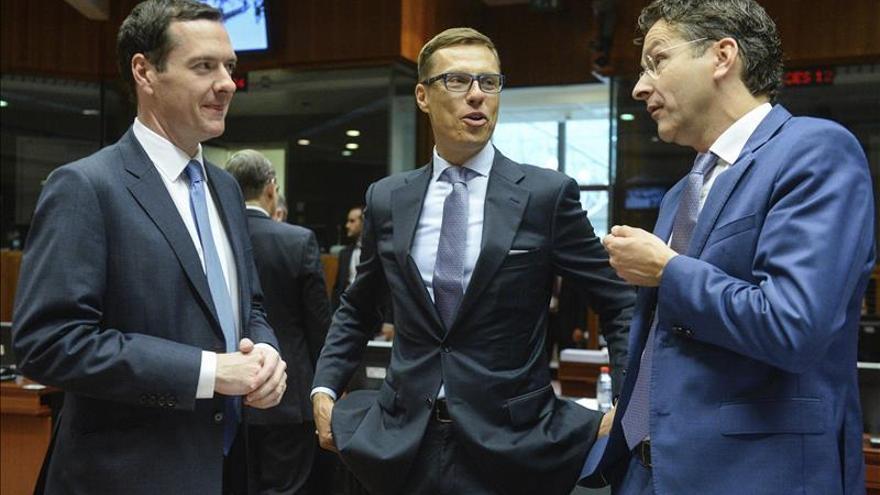 El presidente del Eurogrupo, el holandés Jeroen Dijsselbloem (dcha), habla con el ministro finlandés de Finanzas, Alexander Stubb (centro), y con el titular británico de Economía, George Osborne, en Bruselas (Bélgica).