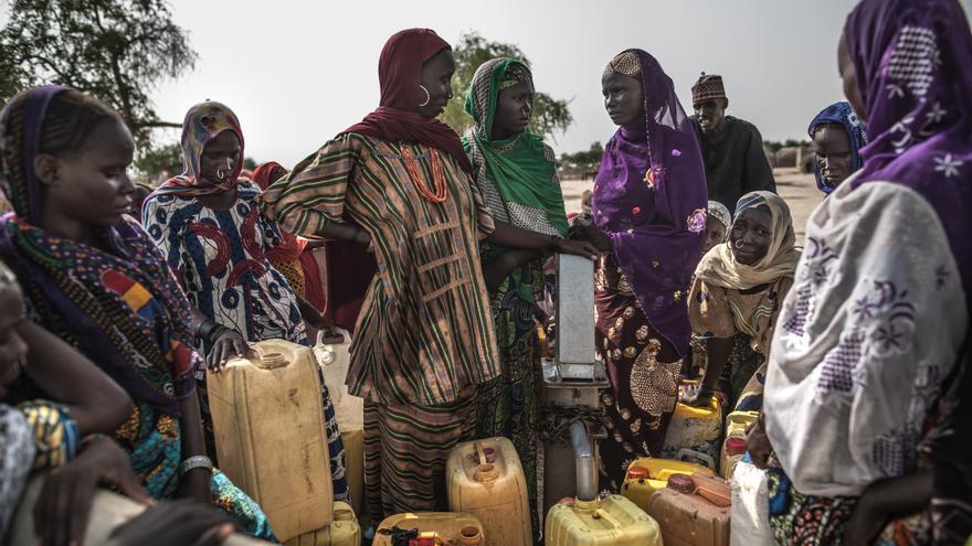 Un grupo de mujeres recogiendo agua de un punto de distribución construido por Oxfam Intermón en la comunidad de Tataverom donde miles de personas buscaron refugio.