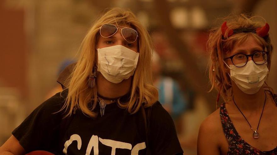 Dos chicas disfrazadas en Santa Cruz de Tenerife, con mascarillas debido a la fuerte calima este domingo