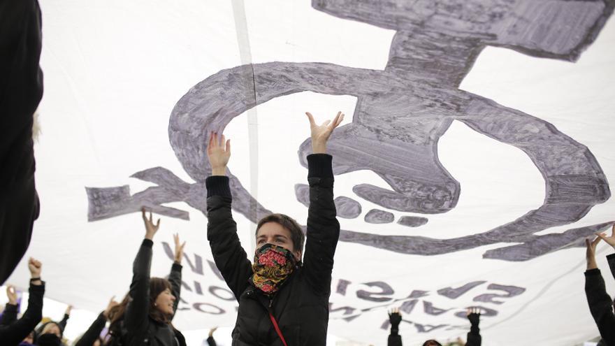 Manifestantes portan una gran pancarta feminista durante el 25N