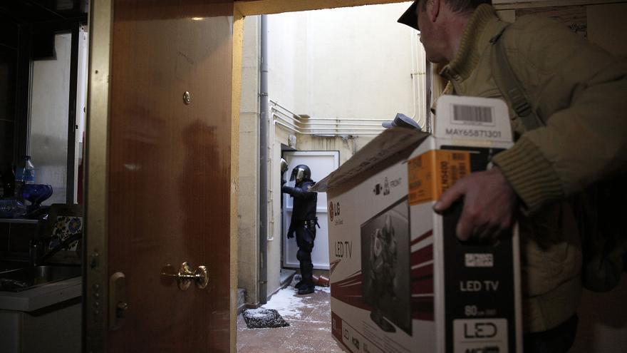 Umberto sacando parte de sus pertenencias mientras la policía permanece en el patio de  entrada de la vivienda. Sólo pudo llevarse una bolsa de deporte y la caja con la televisión que se ve en la fotografía.