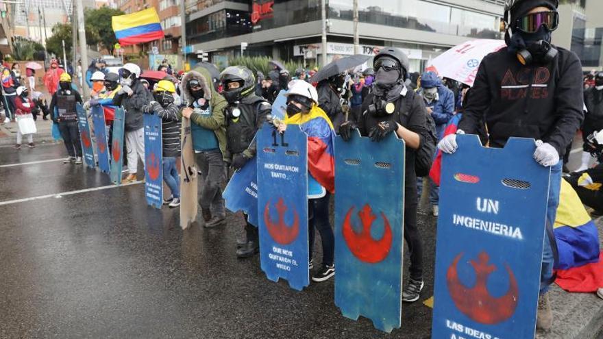 """Integrantes de la llamada """"primera linea"""" de defensa del Paro Nacional sostienen sus escudos caseros mientras participan en una nueva jornada de protestas este martes, en Bogotá (Colombia)."""