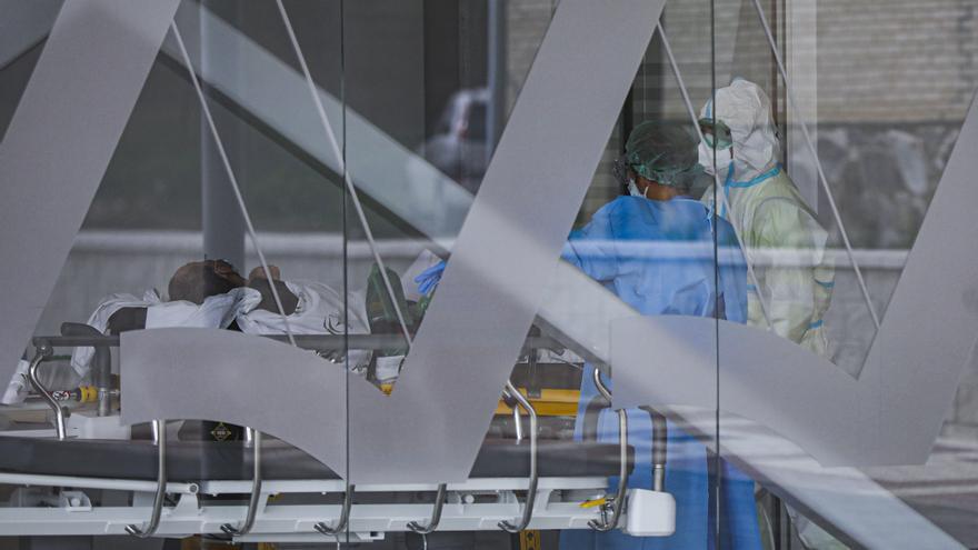 Archivo - Sanitarios con traje EPI durante el ingreso de un paciente covid-19.