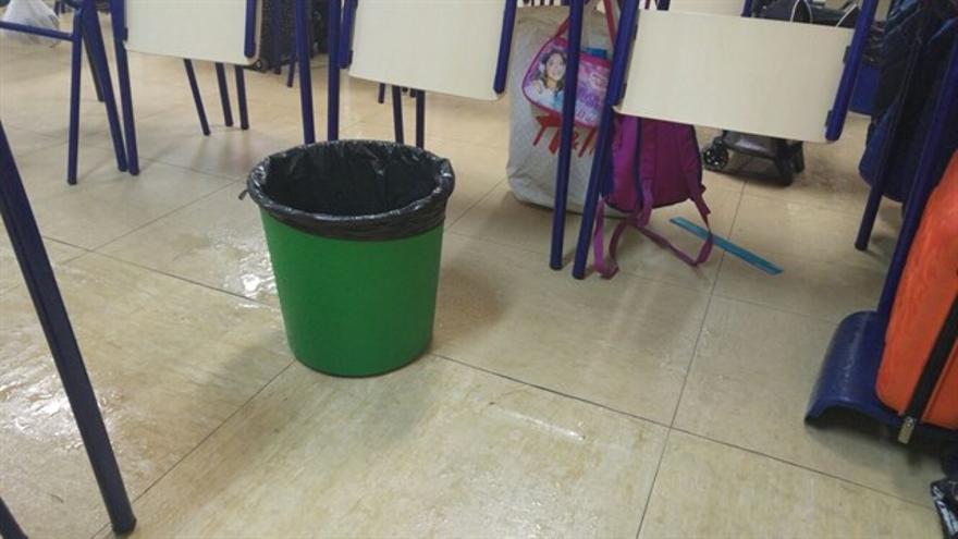 Una papelera recoge el agua que entra en uno de los barracones por las goteras