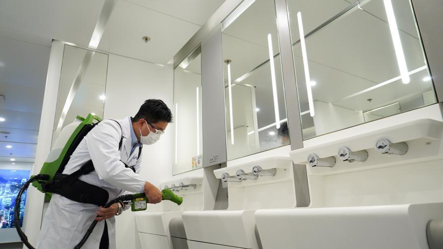 Un trabajador desinfecta los baños del aeropuerto de Hong Kong durante la epidemia de coronavirus