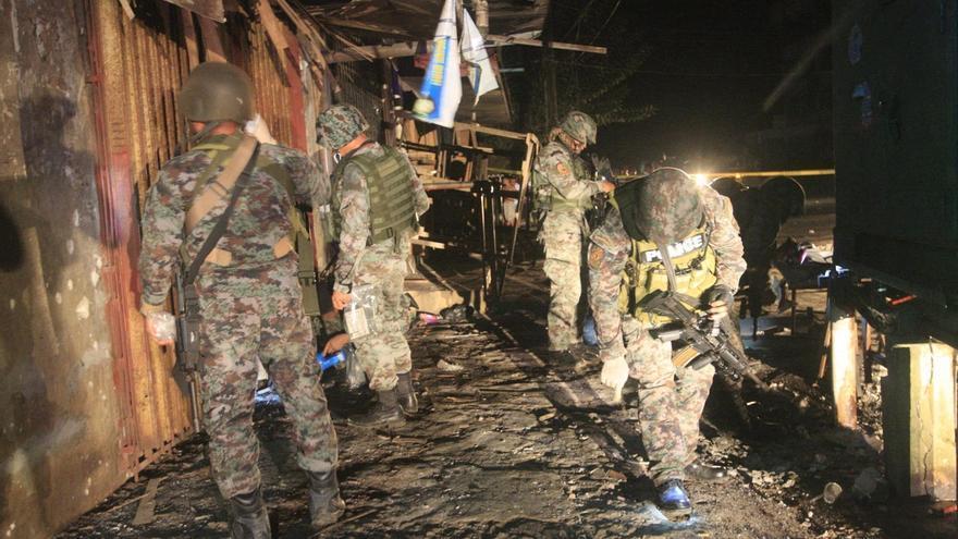Investigadores filipinos registran el lugar de una explosión.