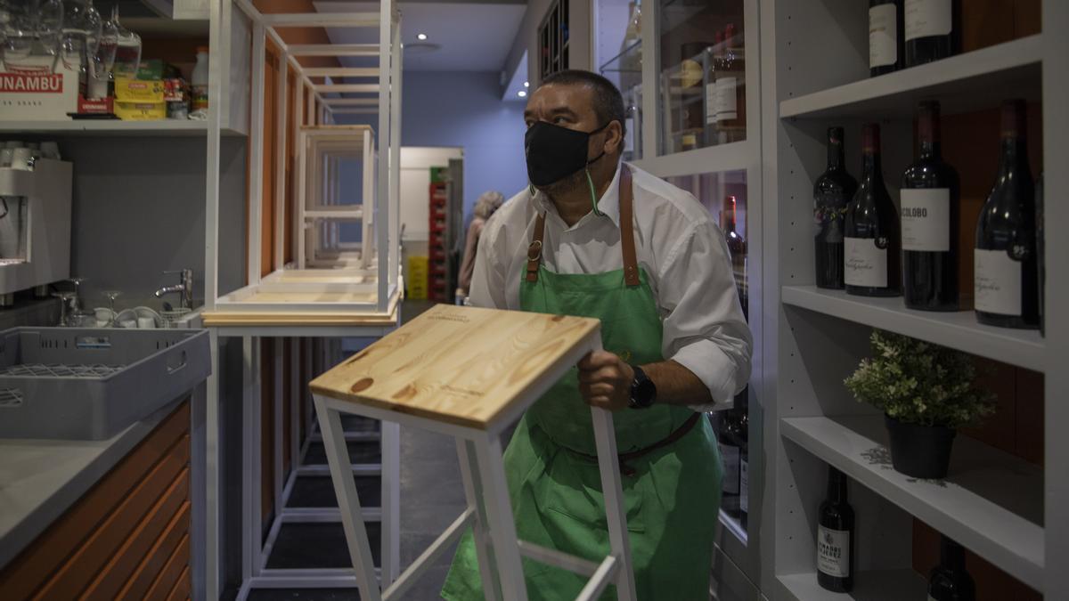 Un hostelero recoge el mobiliario de la terraza de un bar en Sevilla