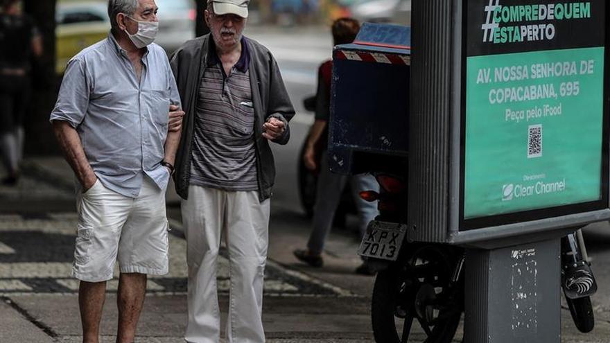 Un adulto mayor ayuda a caminar a un anciano el 10 de abril en el barrio de Copacabana, en Río de Janeiro (Brasil).