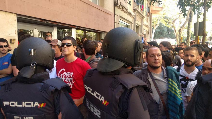 Varios militantes de la CUP, en el exterior de la sede del partido en Barcelona, custodiado por la Policía Nacional.
