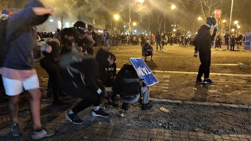 Manifestantes en Barcelona lanzan objetos tras una barricada de contenedores incendiados