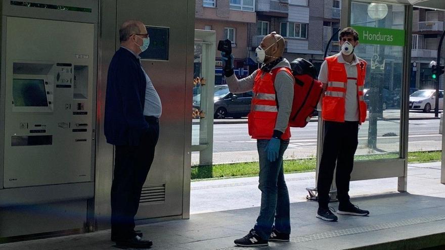 Personal de la Cruz Roja toma la temperatura a un usuario del tranvía de Vitoria