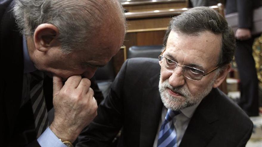 Mariano Rajoy escucha en el Congreso al ministro de Interior, Jorge Fernández Díaz.