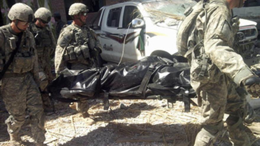Soldados de la coalición transportan compañero muerto en Afganistan