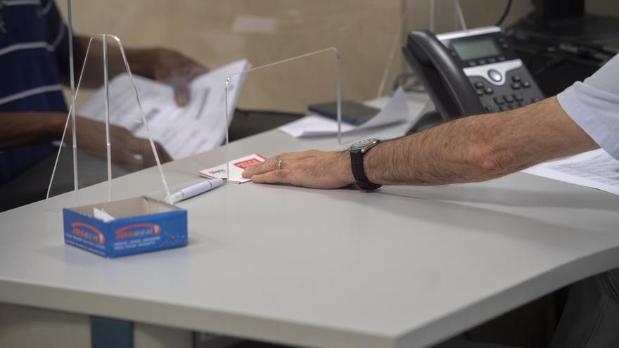 Un empleado atiende a una persona en su puesto de trabajo.
