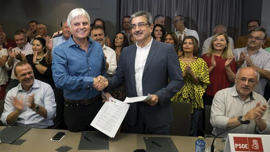 El secretario general del PSOE de Canarias, José Miguel Pérez (2i), y el presidente de Nueva Canarias, Román Rodríguez (2d), se estrechan la mano tras firmar la alianza con que ambas formaciones concurrirán a las elecciones generales de diciembre. (Efe/Ángel Medina).