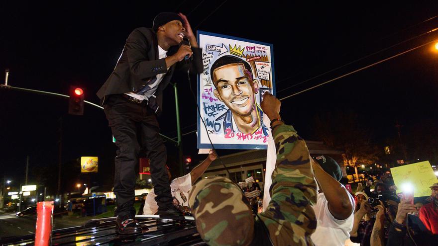 Stevante Clark sostiene una imagen de su hermano fallecido, Stephon, durante un acto de protesta celebrado en Sacramento el pasado viernes.