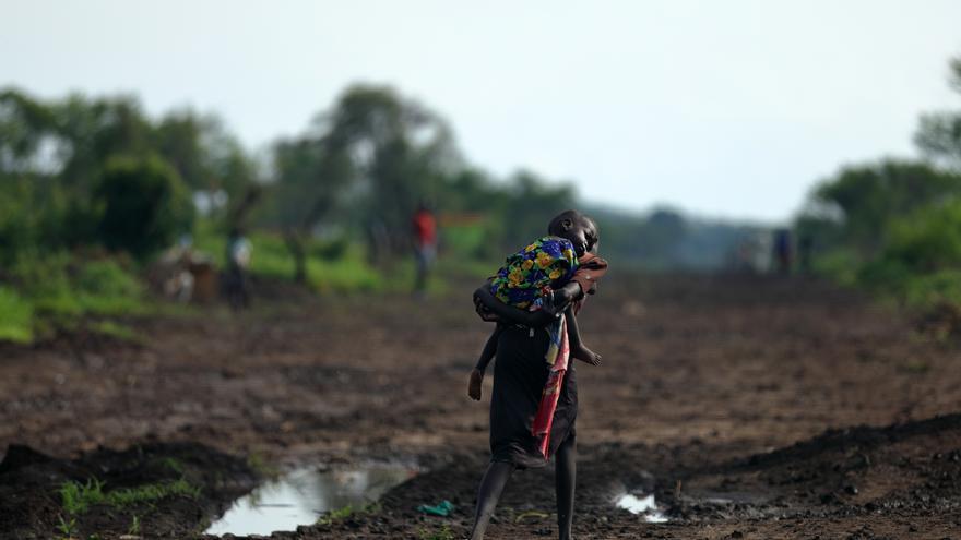Una chica y su hermano, de Sudán del Sur, andan por un camino fangoso. Compartieron el alimento que recibieron. Fotografía: Atsushi Shibuya/MSF