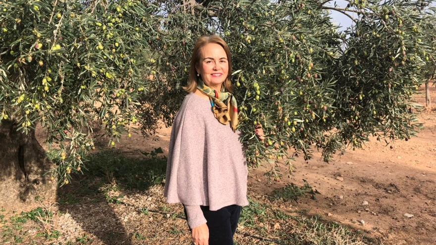 María muestra a eldiario.es/andalucia uno de los olivos que cultiva en su finca de Osuna.