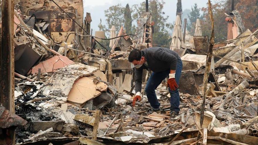 Un hombre busca elementos que puedan recuperarse entre los escombros de un edificio destruido por un incendio en Napa, en California (EEUU)