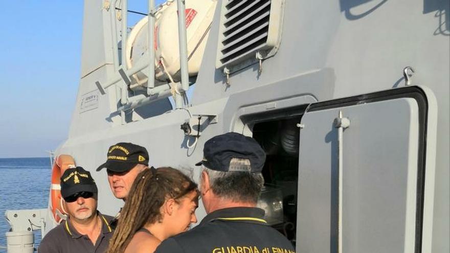 Carola Rackete (c), capitán del buque de rescate Sea Watch 3, es escoltada por oficiales de la Guardia Finanza italiana a bordo de una patrullera en Lampedusa (Italia) en su traslado a la ciudad siciliana de Agrigento, para comparecer ante un tribunal.