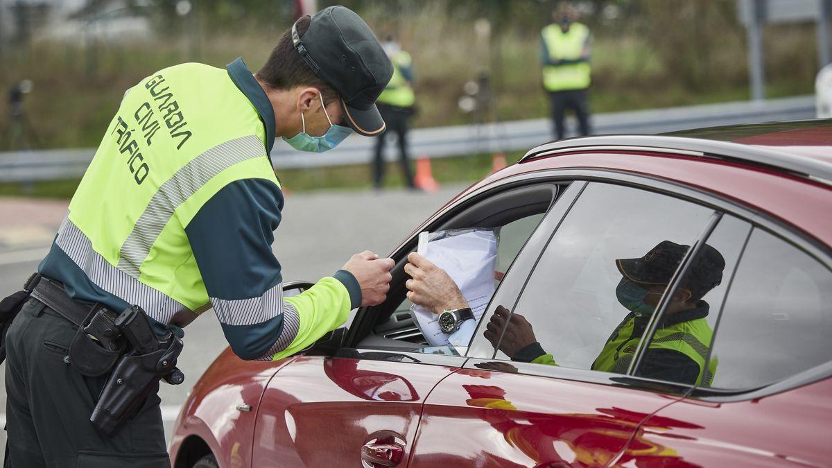 Un agente de la Guardia Civil de Tráfico comprueba la documentación de un conductor en un control policial en la frontera entre Navarra y el País Vasco.