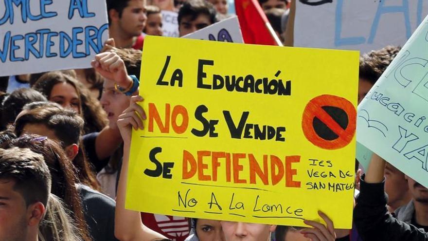 Varios jóvenes con carteles durante la manifestación convocada hoy en Las Palmas de Gran Canaria por los ocho sindicatos representados en la enseñanza pública de Canarias, la Federación de Asociaciones de Padres de Alumnos de Gran Canaria y la Coordinadora de Estudiantes contra las reválidas, los recortes y la Lomce. EFE/Elvira Urquijo A.