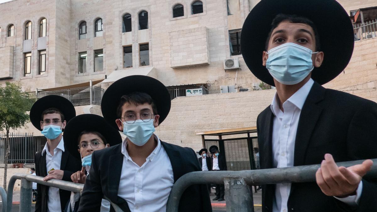 Ultraortodoxos esperan en la parada del autobús en un barrio de Jerusalén antes del toque de queda nocturno para limitar la expansión del virus.