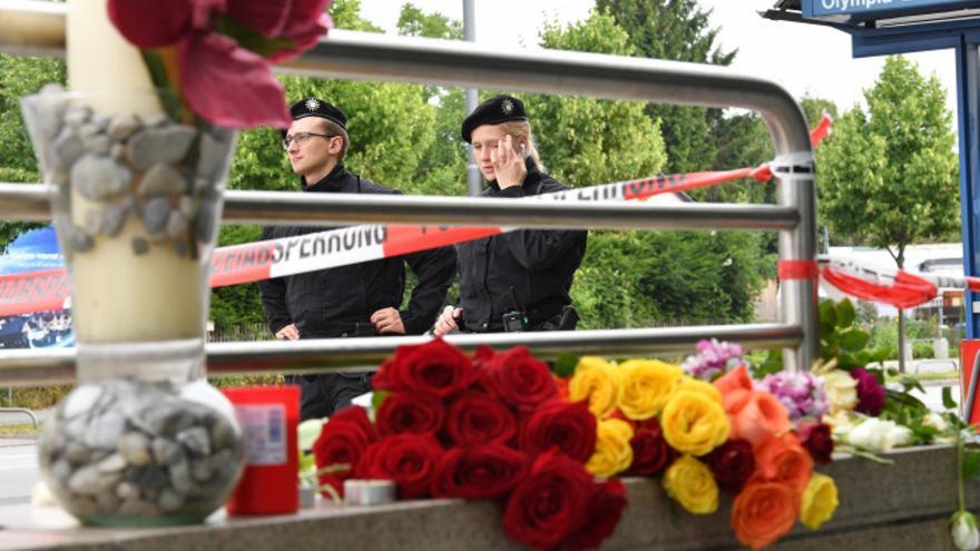 Policías alemanes junto a unas flores en el lugar del tiroteo de Múnich