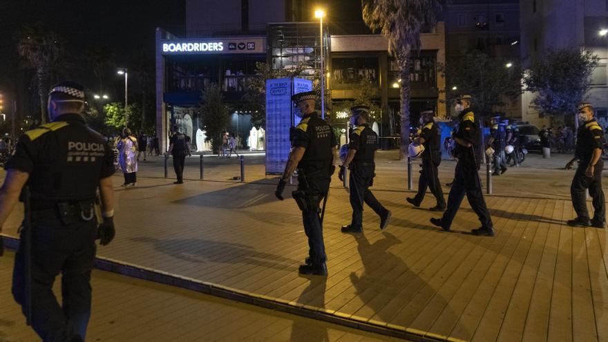 Agentes de la Guardia Urbana forman una línea tras desalojar la playa de la Barceloneta la noche en la que entra en vigor el toque de queda en Cataluña, a 16 de julio de 2021, en Barcelona, Catalunya (España). El Tribunal Superior de Justicia de Cataluña