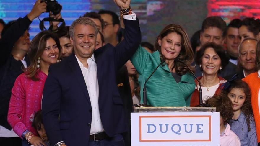 El presidente electo de Colombia, Iván Duque, junto con la futura vicepresidenta, Marta Lucía Ramírez, saludan en su sede de campaña en Bogotá.