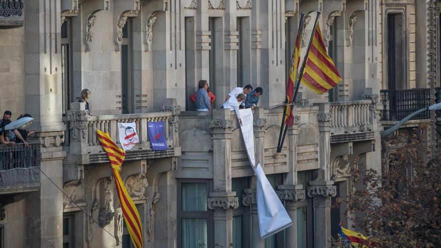 Trabajadores de la conselleria de Economía descuelgan una pancarta con la que piden libertad para los detenidos