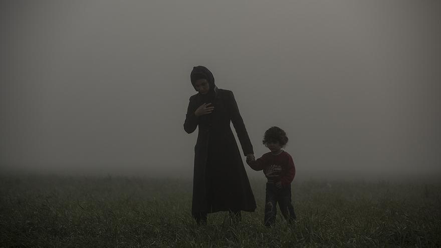 Una madre y su hijo caminando en los alrededores del campo improvisado de Idomeni durante una mañana con mucha niebla. Este campamento, al norte de Grecia junto a la frontera de Macedonia, llegó al albergar a unas 14.000 personas. Idomeni, 08/03/2016. | OLMO CALVO