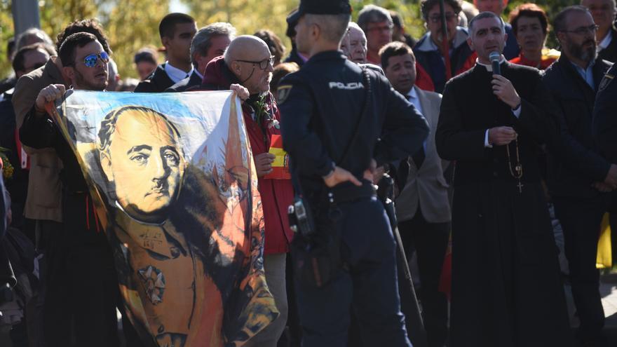 Un grupo de manifestantes con imágenes de Franco reza ante el cementerio de Mingorrubio durante el segundo entierro del dictador.