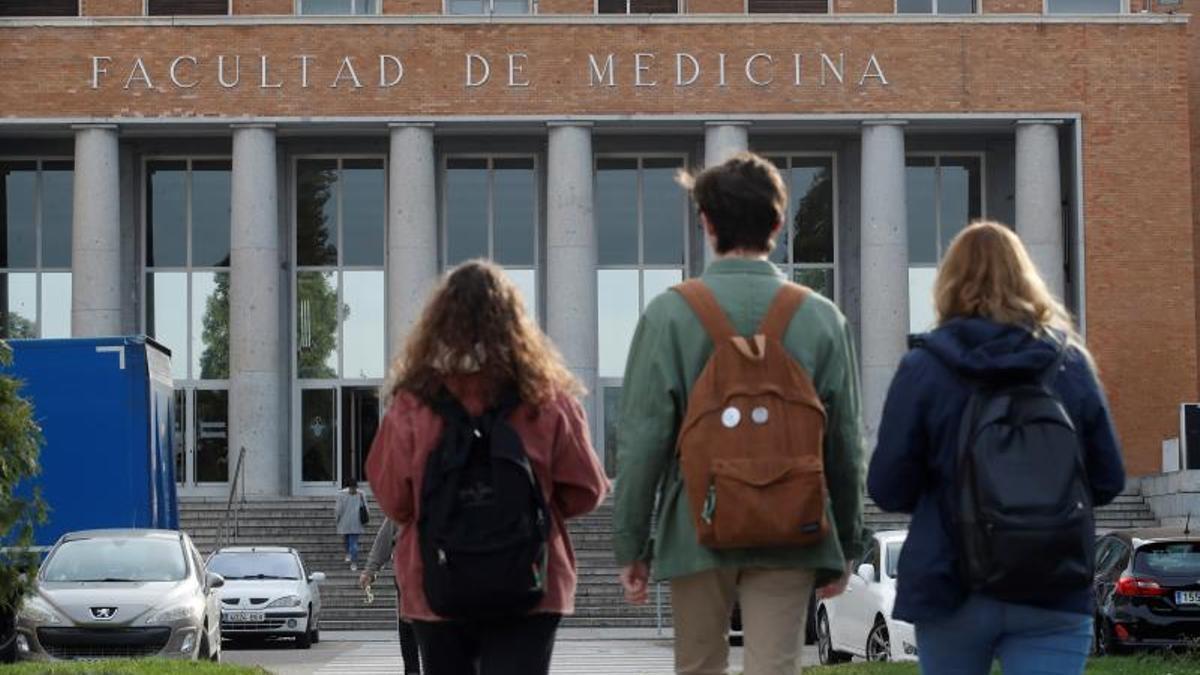 Tres alumnos caminan hacia la Facultad de Medicina.