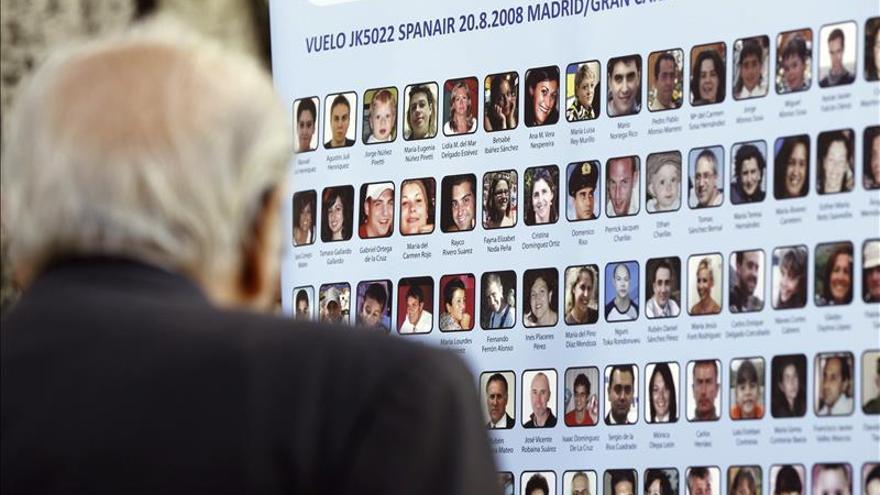 Un hombre observa un cuadro con las fotografías de las víctimas en el accidente de avión de Spanair ocurrido el 20 de agosto de 2008 durante un homenaje.