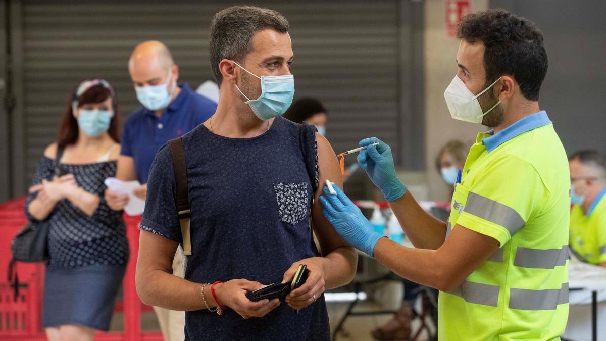 Un enfermero pone la vacuna Pfizer a un hombre en el Estadio Nueva Condomina de Murcia. El Servicio Murciano de Salud ha comenzado a vacunar este viernes a personas de entre 40 y 49 años con las vacunas de Pfizer y Moderna. EFE/Marcial Guillén