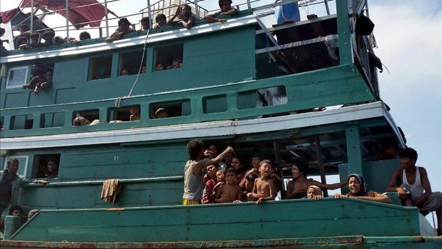Adultos y niños piden ayuda desde un barco a la deriva en el mar de Andaman, cerca de Malasia, al sur de Tailandia, el pasado jueves 14. / EFE.