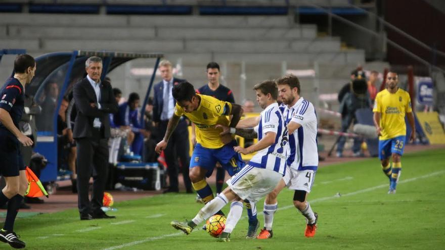 Dos jugadores de la Real Sociedad intentan cortar el avance de Araujo.